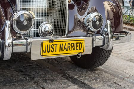 One classical, polished old car used for transportation of wedding with a yellow