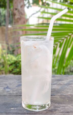 leaves on water: Fresh Coconut Water in a Glass placed on a wooden table.