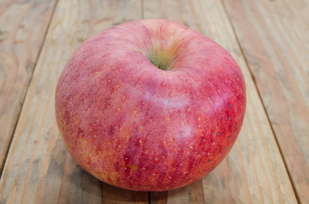 put: Ripe red apple. Put on a wooden table. Stock Photo