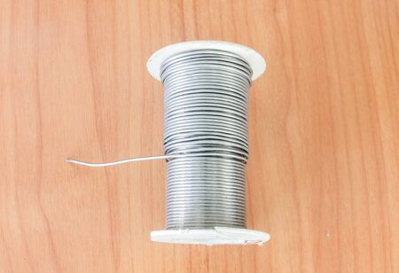 soldered: Reel of Solder placed on a wooden table. Stock Photo