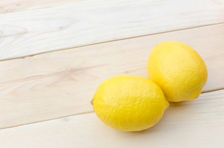 citric: Lemon placed on wooden table.