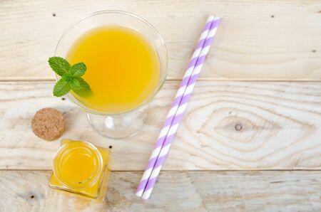 sweet segments: Orange juice in glass on wooden background.
