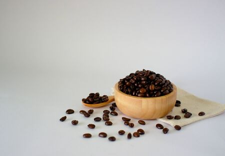 Roasted coffee beans on a white surface, top view with spaces designed for you.