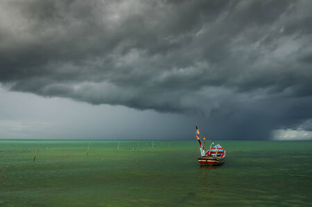 Alone boat with rain cloud out to sea from songkhla, Thailand Photo taken on: October  4th, 2014 photo