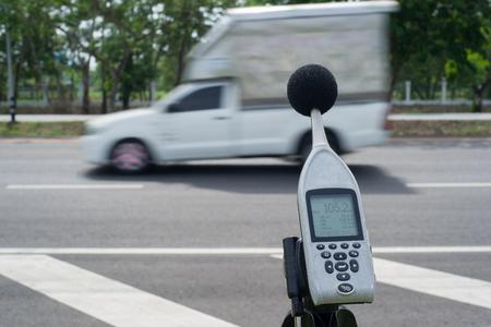 ruido: La medición del ruido de los coches en la carretera con un medidor de nivel de sonido.