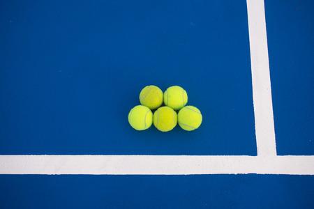Old five tennis balls on tennis court. Stock Photo