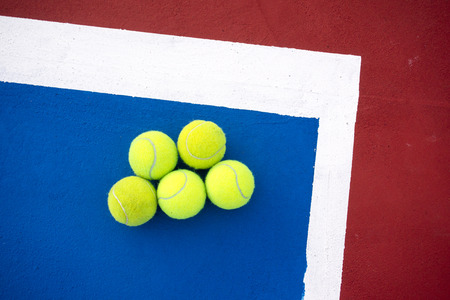 avocation: Old five tennis balls on tennis court