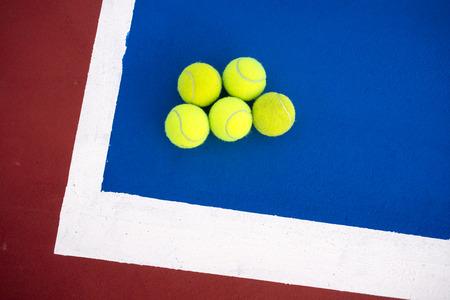 Old five tennis balls on tennis court