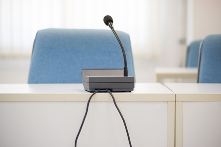 panelist: Selective focus photo of microphone on table in conference room