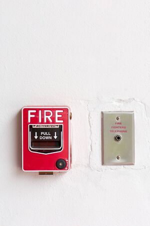 Fire alarm switch and fire  fighters telephone on factory wall Stock Photo