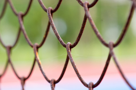 Old metal mesh wire fence with blur background. Stock Photo