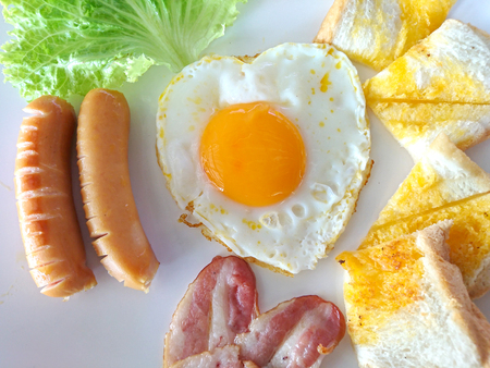 English breakfast: fried egg, bacon, sausage and toast on a plate close-up. horizontal view from above