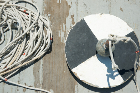 depth measurement: Secchi disk with rope on a wooden dock, water transparency measurement.