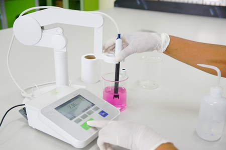 The scientist work at the chemical solution with pH meter