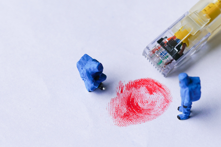 The concept of miniature crime scene investigator with red fingerprint and wired network cable