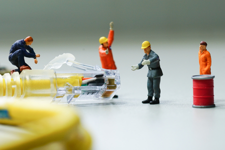 wired: Technicians try to repair cable wire network. Miniature people.