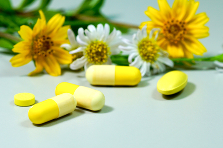 Medicine pills with yellow and white flower.