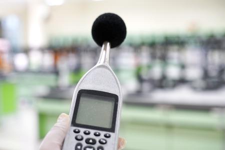 Het meten van het geluid in een laboratoriumruimte met een geluidsniveaumeter. Stockfoto
