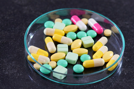 Pharmaceutical medicine pills in petri dish on table