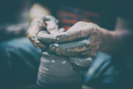 Potter At Work. Man potter making ceramic pot on the pottery wheel Stock Photo