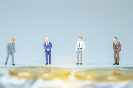 Miniature people : Businessman with golden coin and bills. Business concept.