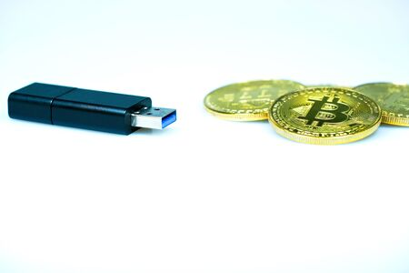 USB flash drive and golden bitcoin on white background