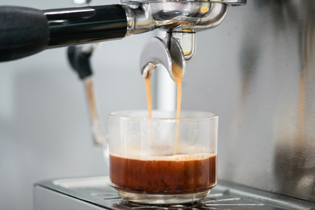 Coffee extraction from coffee machine in the cup Stock Photo