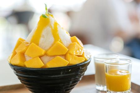 Korean shaved milk ice topped by fresh mango. Mango bingsu.