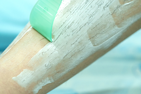Frau epiliert Bein mit Enthaarungscreme und Spachtel. Peeling-Haarentfernungscreme Standard-Bild
