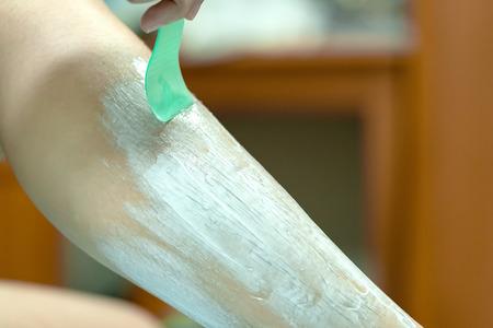 Frau epiliert Bein mit Enthaarungscreme und Spachtel. Peeling-Haarentfernungscreme