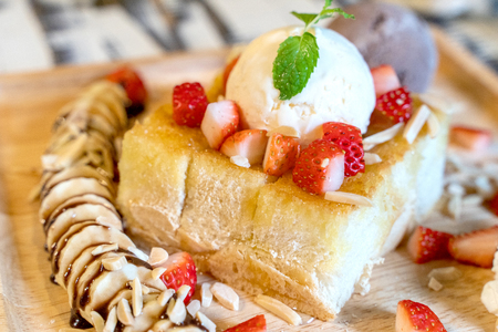 Strawberry honey toast with ice cream on the wood plate dish.