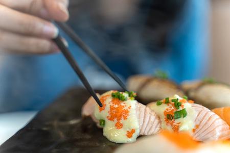 Comer sushi con palillos. Comida japonesa de sushi fresco en el restaurante.