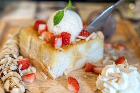 Tostadas de fresa y miel con helado en el plato de madera.