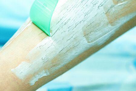 Woman epilating leg with depilation cream and spatula. Scrubs hair removal cream.