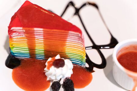 Delicious homemade rainbow layer cake on the plate.