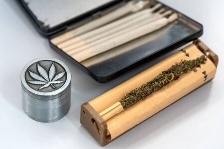 Hands making Marijuana joint from cigarette rolling machine, paper, Making cigarettes with pipe tobacco. Stockfoto
