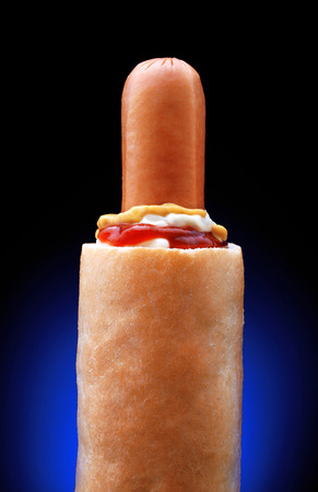 French hot dog with three sauces on black background in vertical position Stock Photo