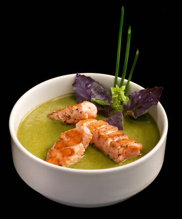 A white bowl of spinach cream soup with salmon isolated on black background Stock Photo