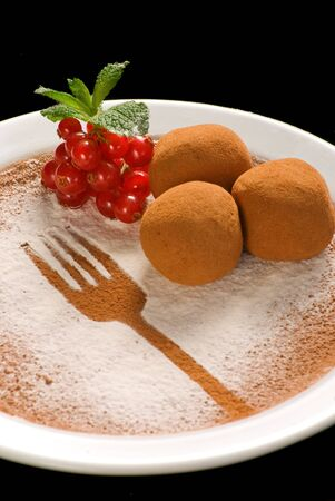 Chocolate truffle with organic cacao on a white plate decorated with fruits and berries
