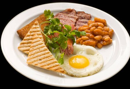 English breakfast: fried egg, bacon, beans and toast on a plate close-up. Banque d'images