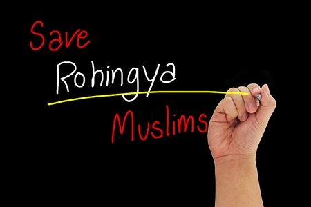 human trafficking: hand with pen writing Save Rohingya Muslims from human trafficking isolated on black background