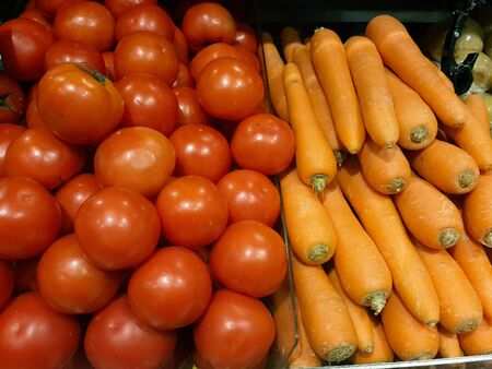 commercialism: Tomato and carrot in grocery store. Stock Photo