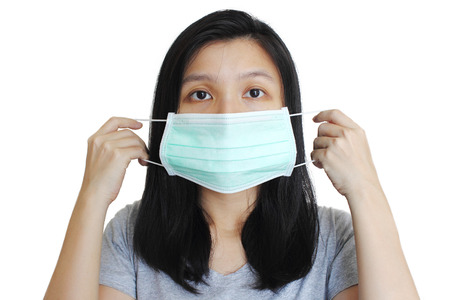 chory: Portrait of Asian woman putting on medical mask on white background.