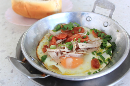 Vietnamese style fried egg in pan with white pork sausage, Chinese sausage, and pork