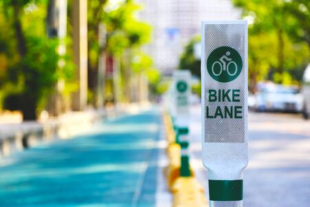 Focus bike lane sign pole in with green tree background. Archivio Fotografico