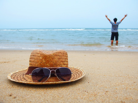 Focus weave hat and sunglasses on sea beach with man raising hands and open arms in the background
