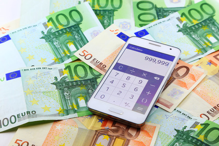 Smart mobile phone open calculator application with euro banknotes on background. Making money online Banco de Imagens