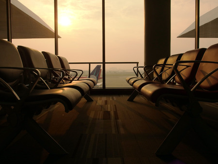 Empty seats in airport waiting lounge with airport and aircraft in background under soft sun light