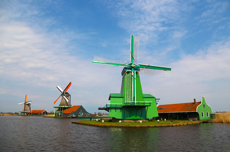 Unique, old, authentic, traditional and colorful dutch windmills along the canal in the suburb area of The Netherlands