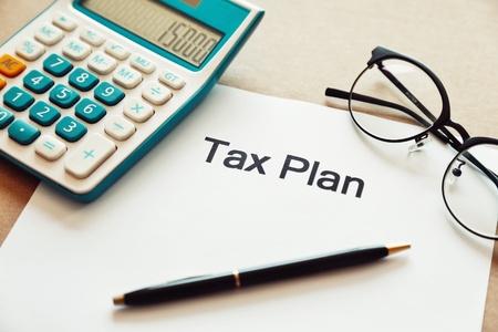Schließen Sie herauf Steuerplanungswort auf Papier mit Taschenrechner-, Stift- und Augenglasplatz auf dem Holztisch.